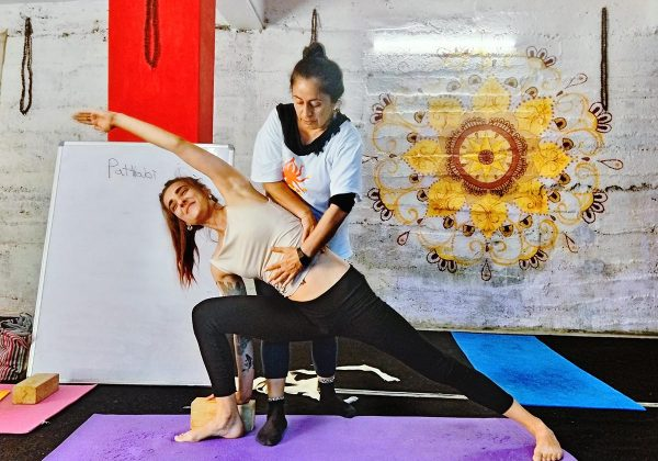 Teacher correcting the posture of the student at 100 hour teacher training course at Shree hari yoga school