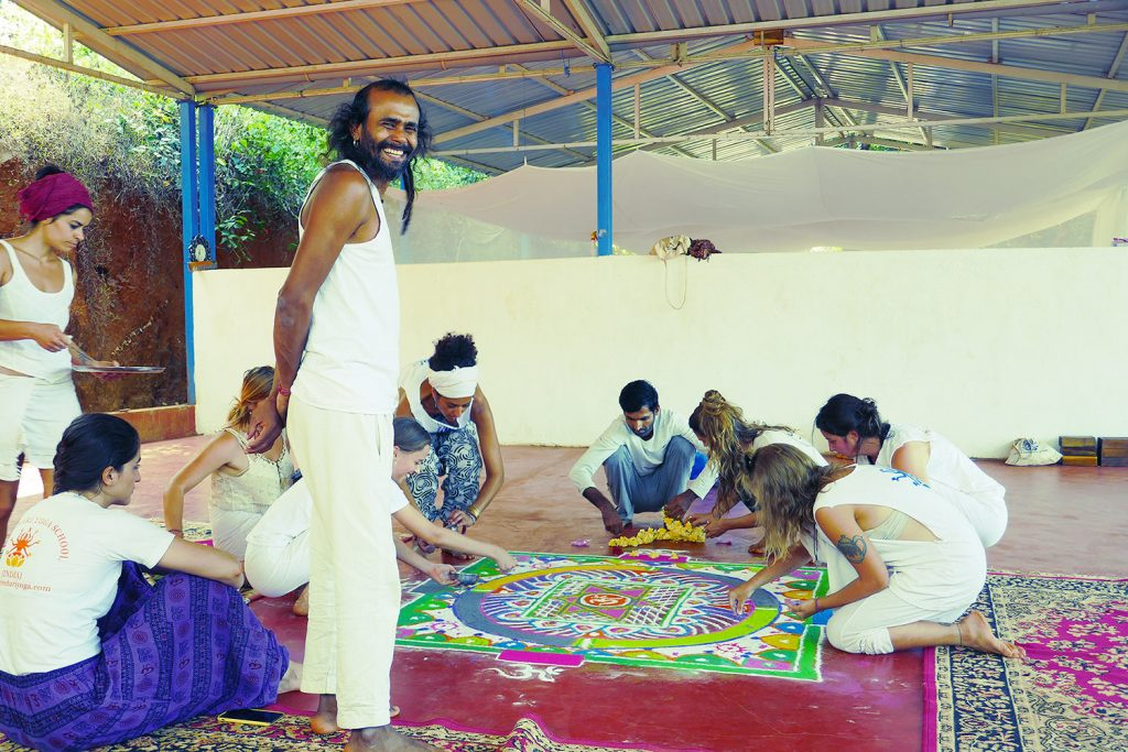 hari pawali owner shree hari yoga with students creating mandala in the yoga school in Gokarna, India